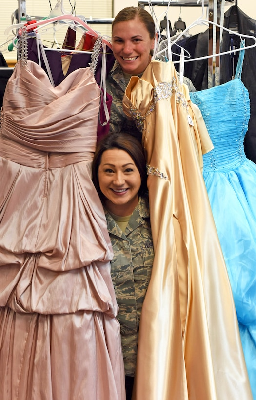 Staff Sgt. Sheena Young, 341st Missile Wing command chief executive, top, and Tech. Sgt. Jenny Johnson-Newman, 341st Medical Operations Squadron NCO in charge of health management, pose for a photograph at the Cinderella's Closet shop March 15, 2016 at Malmstrom Air Force Base, Mont. The shop offers youth, teen and women's dresses for every occasion from formal settings to proms, weddings and receptions. (U.S. Air Force photo/Airman Collin Schmidt)