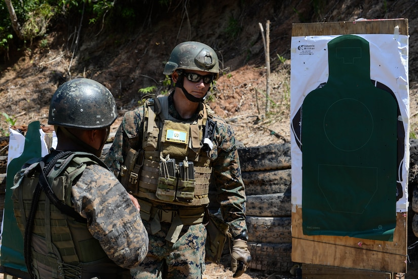 U.S. Marine Sgt. Josh McDonald, instructor, examines a target during range training course with Guatemalan marines March 10, 2016, Guatemala. The Guatemalan marines completed a four-week course with U.S. Marines trainers to hone their skills in small team movements and countering drug traffickers in urban environments. (U.S. Air Force photo by Staff Sgt. Westin Warburton/RELEASED)