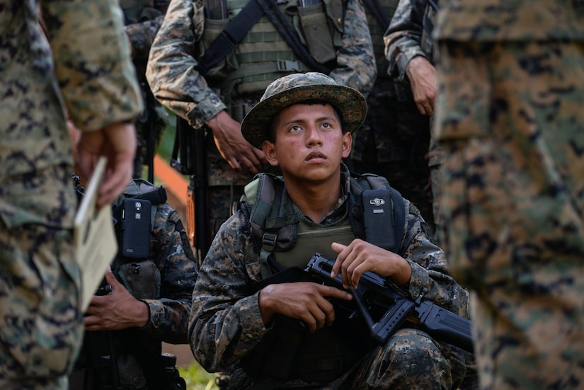 A Guatemalan Marine listens to U.S. Marine instructors explain proper firing range safety procedures March 10, 2016, Guatemala, prior to a live-fire exercise. The Guatemalan marines took part in a four week training course to hone their skills in basic infantry movements and urban operations with the intent of helping them combat drug trafficking organizations. (U.S. Air Force photo by Staff Sgt. Westin Warburton/RELEASED)