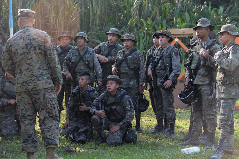 U.S. Marine Staff Sgt. Jorge Avila, instructor, translates directions to Guatemalan marines on proper shooting-range safety March 10, 2016, Guatemala, prior to a live fire skills test. The Guatemalan marines completed a final firing-range assessment before graduating a four week training course in which Marine trainers from a U.S. Marine Security Cooperation Team taught basic infantry maneuvers and how to conduct squad-level movements in an urban environment. (U.S. Air Force photo by Staff Sgt. Westin Warburton/RELEASED)