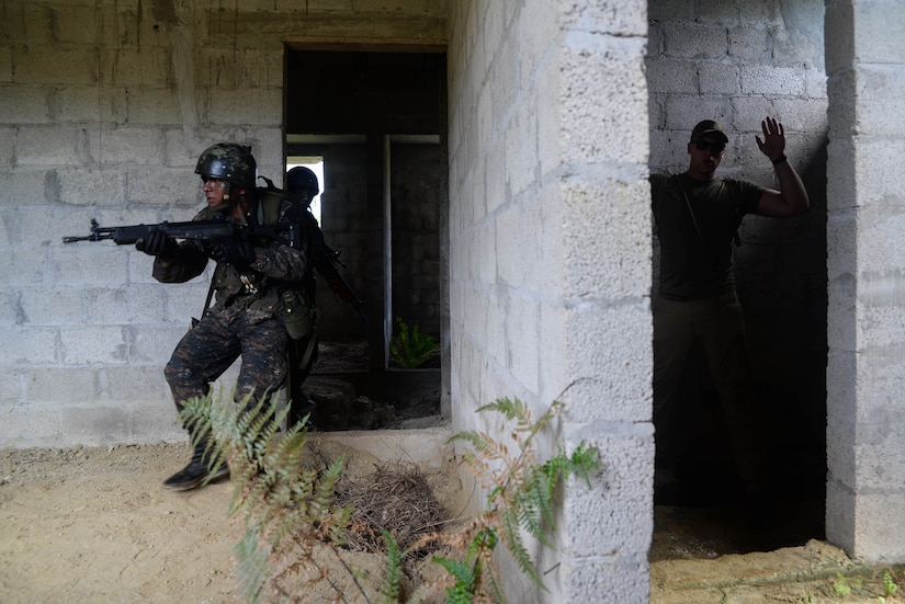 Guatemalan marines sweep a room during an exercise while a U.S. Marine instructor acts as an adversary March 9, 2016, Guatemala. The Guatemalan and U.S. Marines partnered in a four-week course to learn best practices for urban operations and countering drug trafficking organizations in the region. (U.S. Air Force photo by Staff Sgt. Westin Warburton/RELEASED)