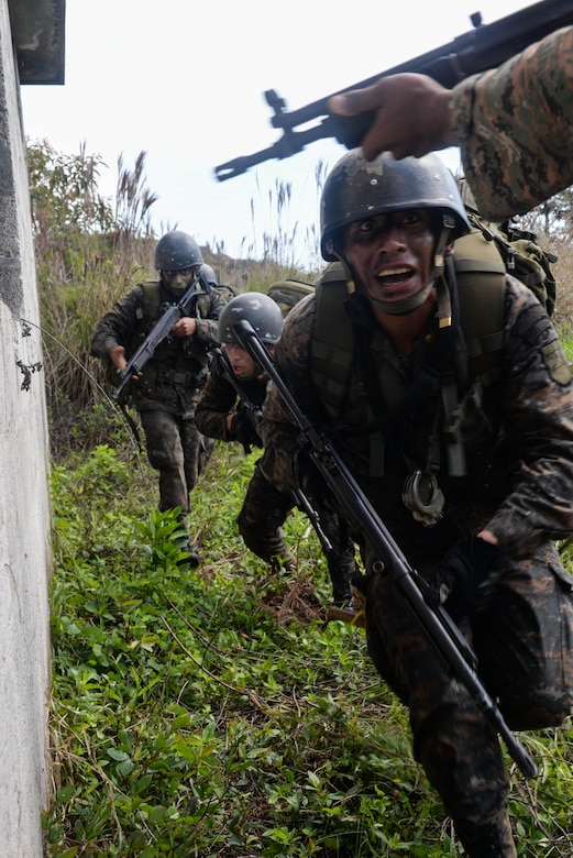 Guatemalan marines enter a house used as an objective March 9, 2016, Guatemala, during the final exercise of a four-week training course. During the course, U.S. Marine trainers provided best practices for small unit movements and how to operate in urban environments against transnational drug trafficking organizations. (U.S. Air Force photo by Staff Sgt. Westin Warburton/RELEASED)