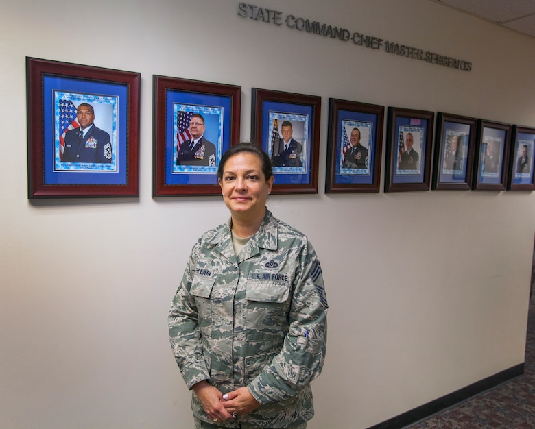 New Jersey State Command Chief Master Master Sgt. Janeen M. Fillari poses in front of the State Command Chief wall at Joint Force Headquarters, New Jersey Air National Guard, at Joint Base McGuire-Dix-Lakehurst, N.J., March 15, 2016. Fillari is the first woman to serve as the New Jersey State Command Chief Master Sergeant for the New Jersey Air National Guard. (U.S. Air National Guard photo by Master Sgt. Mark C. Olsen/Released)