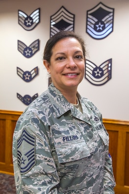 New Jersey State Command Chief Master Master Sgt.  Janeen M. Fillari stands in front of a wall displaying all the enlisted ranks at Joint Force Headquarters, New Jersey Air National Guard, at Joint Base McGuire-Dix-Lakehurst, N.J., March 15, 2016. Fillari is the first woman to serve as the New Jersey State Command Chief Master Sergeant for the New Jersey Air National Guard. (U.S. Air National Guard photo by Master Sgt. Mark C. Olsen/Released)