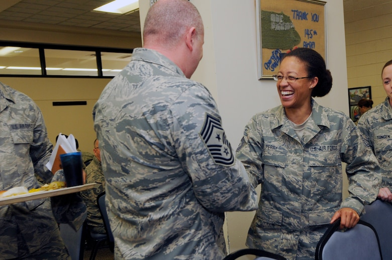 U.S. Air Force Tech. Sgt. Carissa Perry (right), 145th Communications Flight cyber systems operations, shakes hands with Command Chief Master Sergeant of the Air National Guard James W. Hotaling during a lunch with Airmen at the North Carolina Air National Guard Base, Charlotte Douglas International Airport, March 12, 2016. Hotaling gave advice on how to be successful, and talked about his focus on renewing the profession of arms. (U.S. Air National Guard photo by Staff Sgt. Julianne M. Showalter/Released)