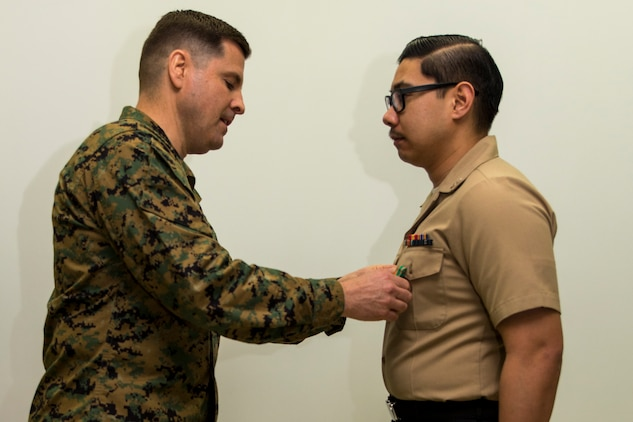 Col. Robert V. Boucher, left, commanding officer of Marine Corps Air Station Iwakuni, pins the Navy and Marine Corps Achievement Medal on Petty Officer 3rd Class Jason Aguirre, a logistics specialist with Headquarters and Headquarters Squadron, after Aguirre was awarded with Marine Corps Installations Pacific Junior Sailor of the Year at MCAS Iwakuni, Japan, March 10, 2016. Aguirre said becoming Sailor of the Year wasn't an easy task and participating in Marine Corps activities helped him achieve his newly appointed title. Aguirre said he is grateful for the award and plans to keep on bettering himself. (U.S. Marine Corps photo by Lance Cpl. Aaron Henson/Released)