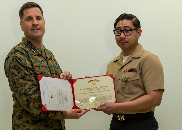 Petty Officer 3rd Class Jason Aguirre, right, a logistics specialist with Headquarters and Headquarters Squadron, poses for a photo with Col. Robert V. Boucher, commanding officer of Marine Corps Air Station Iwakuni, after being awarded the Marine Corps Installations Pacific Junior Sailor of the Year at MCAS Iwakuni, Japan, March 10, 2016. Aguirre said becoming sailor of the year wasn't an easy task and participating in Marine Corps activities helped him achieve his newly appointed title. (U.S. Marine Corps photo by Lance Cpl. Aaron Henson/Released)
