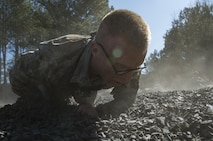 Tech. Sgt. Dylan Bolander, a 3rd Combat Camera Squadron broadcaster, crawls through the final obstacle of a team building event during exercise Scorpion Lens March 6, 2016, at Fort Jackson, S.C. The purpose of the exercise was to provide refresher training to combat camera personnel of all ranks and skill levels in basic tactics, techniques, and procedures inherent to combat camera mission tasking. (U.S. Air Force photo/Staff Sgt. Perry Aston)