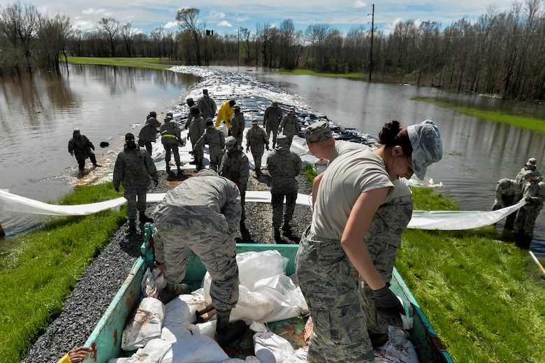 Airmen from Barksdale Air Force Base, La., build a protective barrier over a levee in Bossier City, La., March 10, 2016. Airmen worked in unison with the Army Corps of Engineers and local city employees to transport, unload and place sandbags at the lowest sections of the Red Chute Bayou levee. (U.S. Air Force photo/Senior Airman Mozer O. Da Cunha)
