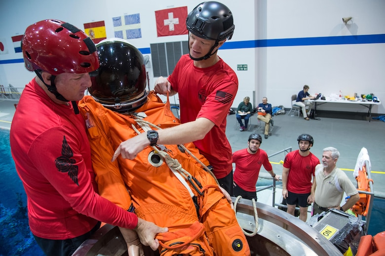 "Master Sgt. Chris Seinkner, 308th Rescue Squadron, located at Patrick AFB, Fla., teams up with Tech. Sgt. Cameron Hystad, 88th Test and Evaluation Squadron, Nellis AFB, Nev., to exercise egressing a ""NASA astronaut"" through the docking hatch (top hatch) of the Orion Capsule under the guidance of the 45th Operations Group's Detachment 3 during a recent exercise at NASA's Neutral Buoyancy Lab in Houston, Texas. The Air Force and NASA work together to prepare for contingency landing site support, payload security, medical support, coordination of airlift/sealift for contingency operations, as well as other support services required in the event of a spacecraft emergency. Detachment 3 was chartered in 1959 by the Secretary of Defense as the DoD Mercury Support Office [later renamed DoD Manned Space Flight Support Office (DDMS)], its express purpose is providing DoD support to our nation's human space flight programs, putting people into space and returning them safely to Earth. (Courtesy photo/NASA)"