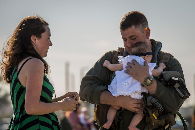 A pilot greets his family on the flightline aboard Marine Corps Air Station Beaufort March 15. More than 180 Marines and 10 F/A-18D Hornet aircraft have been deployed to the Western Pacific since October 2015 as part of the Unit Deployment Program. The pilot is with VMFA(AW)-224.