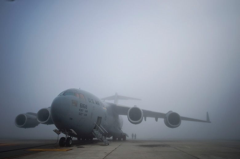 On a foggy flightline, Tech. Sgt. Christine King (right), 512th Airlift Wing, and Airman 1st Class Anthony Mahon, 436th Airlift Wing, walk to the rear of a Team Dover C-17 Globemaster III to train on aircraft marshalling procedures on Dover Air Force Base, Del., March 17, 2016. Experienced reservists from the 512th Airlift Wing frequently train active-duty Airmen in various career field tasks. (U.S. Air Force photo/ Capt. Bernie Kale)