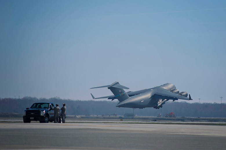 Team Dover maintenance personnel watch as a C-17 Globemaster III takes off from Dover Air Force Base, Del., March 17, 2016. Reservists and active duty Airmen work side-by-side daily in the maintenance and other career fields, promoting Total Force Integration within Team Dover. (U.S. Air Force photo/ Capt. Bernie Kale)