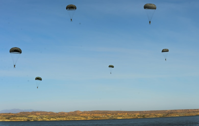 Pararescuemen assigned to the 58th Rescue Squadron at Nellis Air Force Base, Nevada, prepare to land on Lake Mead after preforming static line jumps March 15, 2016. All PJs are qualified experts in Advanced Weapons and Small Unit Tactics, Airborne and Military Free Fall, Combat Divers, High Angle/Confined Space Rescue operations, Small Boat/Vehicle Craft utilization, Rescue Swimmers, and Battlefield Trauma/Paramedics. (U.S. Air Force photo by Airman 1st Class Kevin Tanenbaum)