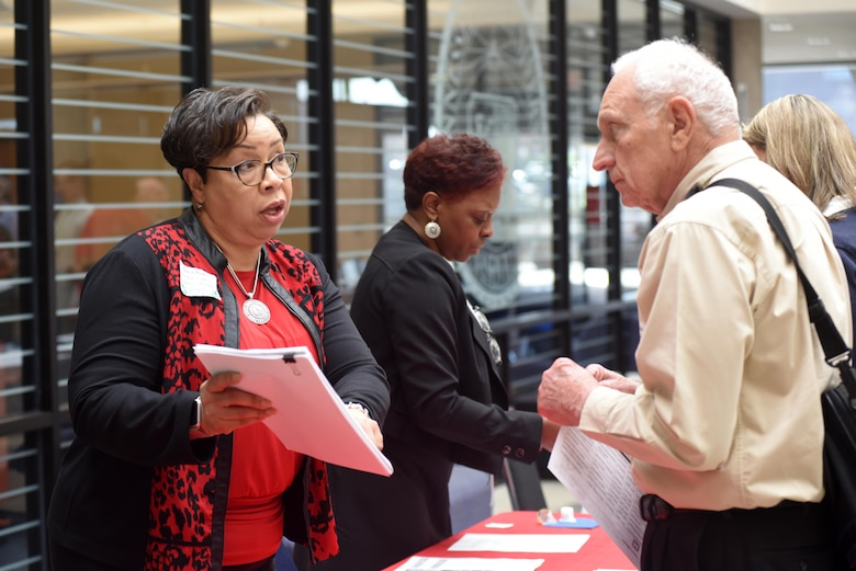 Karen Brady (Left), U.S. Army Corps of Engineers Memphis District Small Business Program manager, and Estella Blackman, also from the Memphis District, assist Jim Speakman of Powers Hill Designs LLC., during the 5th Annual Small Business Forum at Tennessee State University in Nashville, Tenn., March 17, 2016.
