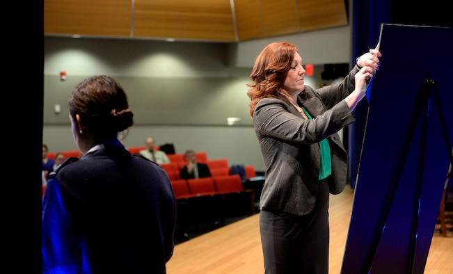 Lisa Surette, a participant of a Sexual Assault Awareness Month event hosted by the Air Force's top leaders at the Pentagon March 17, 2016, pins to a sign a sexual assault victim's testimonial, which she read aloud to event attendees. (U.S. Air Force photo/Scott M. Ash)