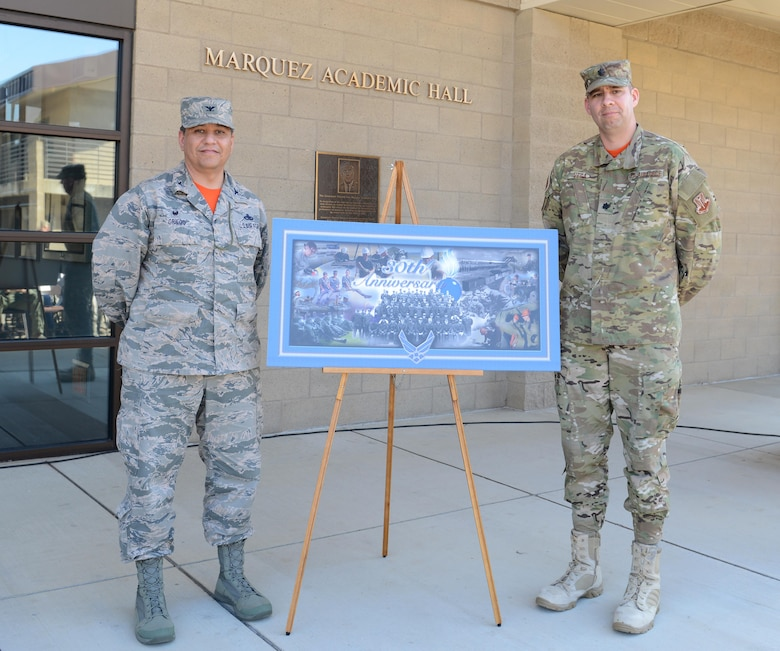 Col. Manuel Griego (left), 9th Maintenance Group commander, and Lt. Col. Frank Vega, 9th Munitions Squadron commander, reveal a commemorative poster celebrating the Air Force Combat Ammunition Center's (AFCOMAC) 30th Anniversary March 18, 2016, at Beale Air Force Base, California. Thirty years ago, AFCOMAC was developed to provide the Air Force munitions community advanced combat training in mass munitions planning and production techniques. (U.S. Air Force photo by Senior Airman Bobby Cummings)