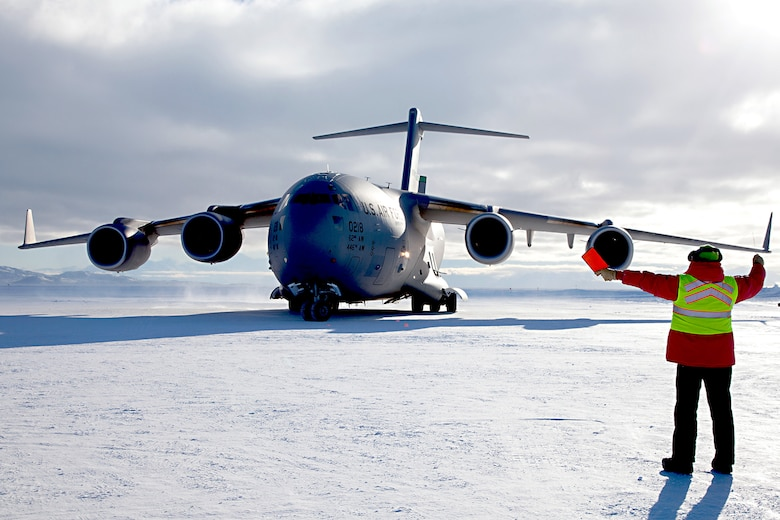 """A C-17 Globemaster III aircraft out of Joint Base Lewis-McChord, Washington, is marshaled on Pegasus Runway, Antarctica during the 2015 Operation Deep Freeze Season. The 446th Airlift """"Rainier"""" Wing partners with its sister unit, the 62nd Airlift Wing, in a total force Team McChord effort to provide airlift support to the Antarctic Program, which manages three research stations year round. (Courtesy photo)"""