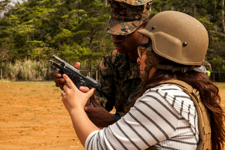 Yukiko Roman shoots an M9 service pistol at Camp Schwab, Okinawa, Japan, March 18, 2016. Roman was able to experience dynamic facets of life in the Marine Corps. This included an Amphibious Assault Vehicle raid, firing the M16-A4 service rifle, firing the M240B medium machine gun, wearing flak jackets with Kevlar helmets and eating packaged military rations. Roman is an Okinawa resident and married to a Marine with Combat Assault Battalion, 3rd Marine Division, III Marine Expeditionary Force. (U.S. Marine Corps photo by Pfc. Nelson B. Duenas /Released)