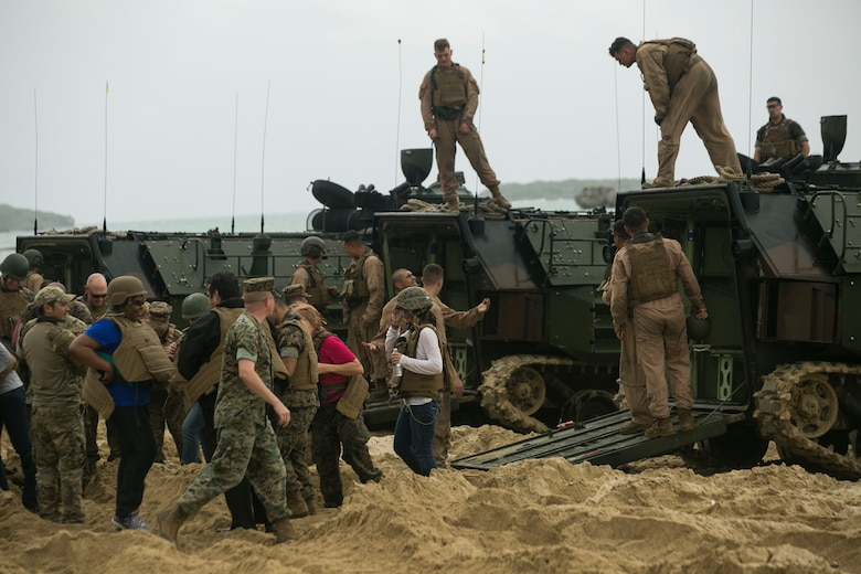 """Marines and their family members put on flak jackets and Kevlar helmets, preparing to """"splash"""" on an Amphibious Assault Vehicle during a Jane Wayne event on Camp Schwab, Okinawa, Japan, March 18, 2016. The Jane Wayne event allows Marine family members to get a first-hand experience of what they do every day. The Marines and family are with Combat Assault Battalion, 3rd Marine Division, III Marine Expeditionary Force. (U.S. Marine Corps photo by Cpl. William Hester/ Released)"""