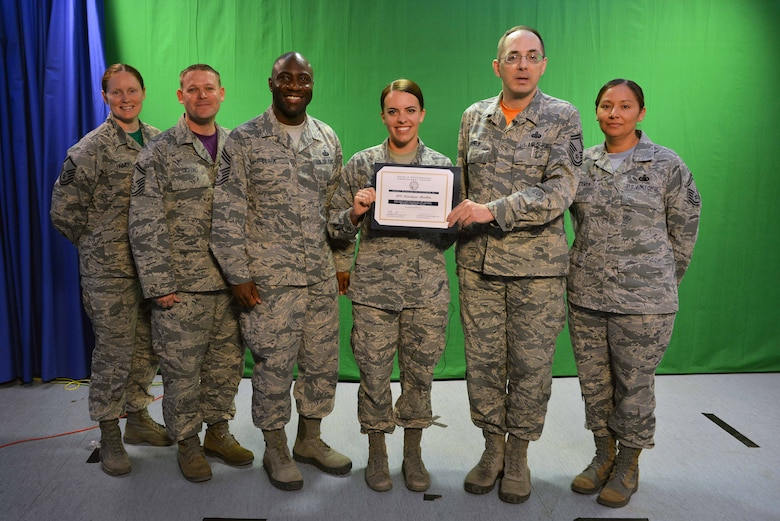 "The Incirlik Air Base Top 3 presents U.S. Air Force Airman 1st Class Katie Moeller (middle), American Forces Network Incirlik broadcast producer, with a Titan University, ""wingman level"" award, March 11, 2016, at Incirlik Air Base, Turkey. Currently, Moeller has completed 11 classes spanning 11 hours total toward her Titan University education. (U.S. Air Force photo by Senior Airman John Nieves Camacho/Released)"