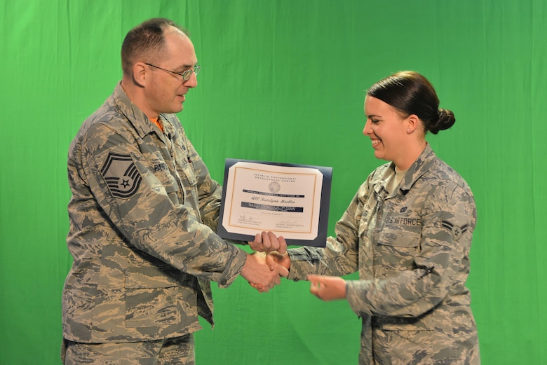 "U.S. Air Force Senior Master Sgt. Kevin Pawlik, 39th Communications Squadron plans and programs flight superintendent, presents U.S. Air Force Airman 1st Class Katie Moeller, American Forces Network Incirlik broadcast producer, with a Titan University, ""wingman level"" award, March 11, 2016, at Incirlik Air Base, Turkey. The wingman level award requirements consist of three core classes, one intermediate class, one primary class, and a two-page essay. (U.S. Air Force photo by Senior Airman John Nieves Camacho/Released)"