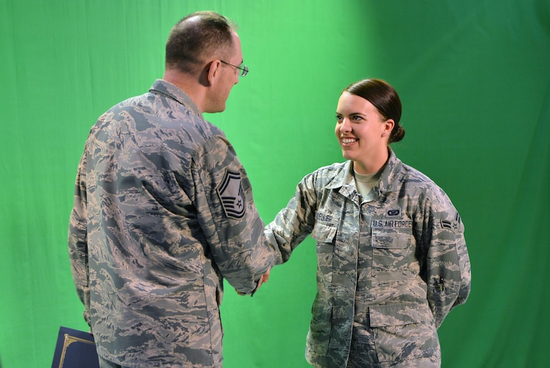 "U.S. Air Force Senior Master Sgt. Kevin Pawlik, 39th Communications Squadron plans and programs flight superintendent, congratulates U.S. Air Force Airman 1st Class Katie Moeller, American Forces Network Incirlik broadcast producer, March 11, 2016, at Incirlik Air Base, Turkey. Moeller was recognized by the Incirlik Top 3 and presented with a Titan University, ""wingman level"" award, for completing five classes within the program. (U.S. Air Force photo by Senior Airman John Nieves Camacho/Released)"