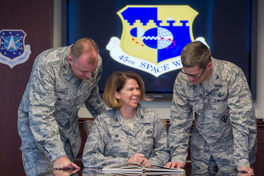 Colonels Daniel Gottrich, 45th SW chief of  safety, Shannon Klug, 45th Weather Squadron commander, and Shawn Fairhurst, 45th Space Wing vice commander, look over their high school's yearbook and share memories of attending James W. Robinson Secondary School in Fairfax, Va., in the late 1980s. Fairhurst's senior photo is in Klug's 1986 yearbook where she was featured as a junior. She graduated in 1987 and Gottrich graduated in 1988. The yearbook pages prove the three former Robinson Rams who were once strangers are now Air Force Wingmen, leading extraordinary missions from the nation's gateway to space. (U.S. Air Force photo by Matthew Jurgens/released)