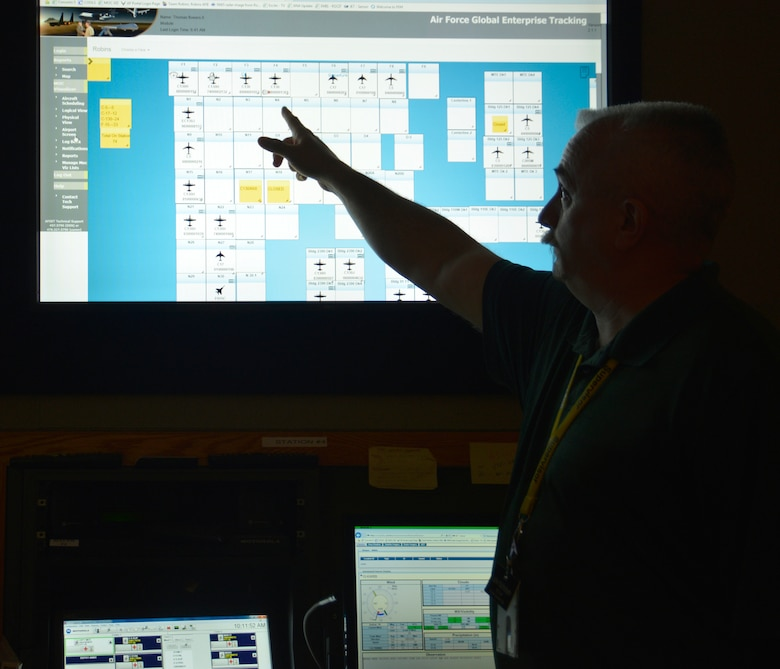 John Nicholson, Maintenance Operations Center chief, shows aircraft locations on the Maintenance Operations Center Visualizer. The MOC is a 24/7 operation that assists efforts on the Robins flight line. The MOC's responsibilities are varied, from supporting maintenance professionals with aerospace ground equipment and tracking injuries and incidents, to alerting personnel of inclement weather and keeping eyes on the locations of every aircraft on station. (U.S. Air Force photo by Ed Aspera)