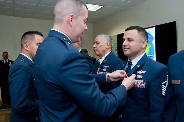 MIAMI - Colombian Air Force Lt. Edgardo J. Villamizar pins the Colombian Air Defense and Air Navigation medal here, March 4 on U.S. Air Force Master Sgt. Juan P. Castro, assigned to the I.G. Brown Training and Education Center. (U.S. Air National Guard photo by Master Sgt. Betty J. Squatrito-Martin/Released)