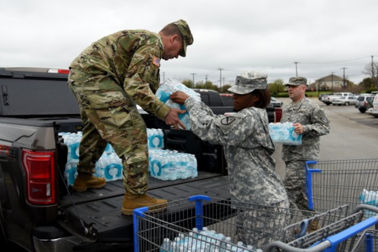 Maj. George Hurd, left, Staff Sgt. Erdoo Thompson, center, and 1st Lt. Matthew Verdugo, right, all of the 136th Maneuver Enhancement Brigade, load bottled water in preparation for Hurd's convoy to Flint, Michigan, March 10, 2016, in Round Rock, Texas.