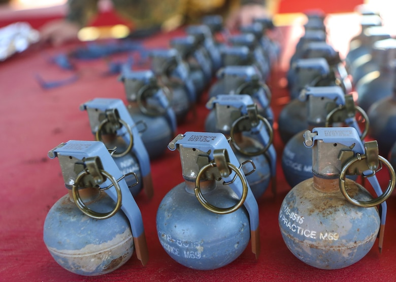 Inert grenades (dummy), non-exploding practice tools, sit on a table where Marines with 2nd Law Enforcement Battalion will pick them up before taking part in an assault course with grenade training at Camp Lejeune, N.C., March 16, 2016. This drill is part of an annual training event to prepare them for combat situations when they are called upon to deploy. Marines took turns providing cover fire for their partner, allowing them to throw a dummy grenade near the simulated enemy position (U.S. Marine Corps photo by Lance Cpl. Aaron K. Fiala/Released)
