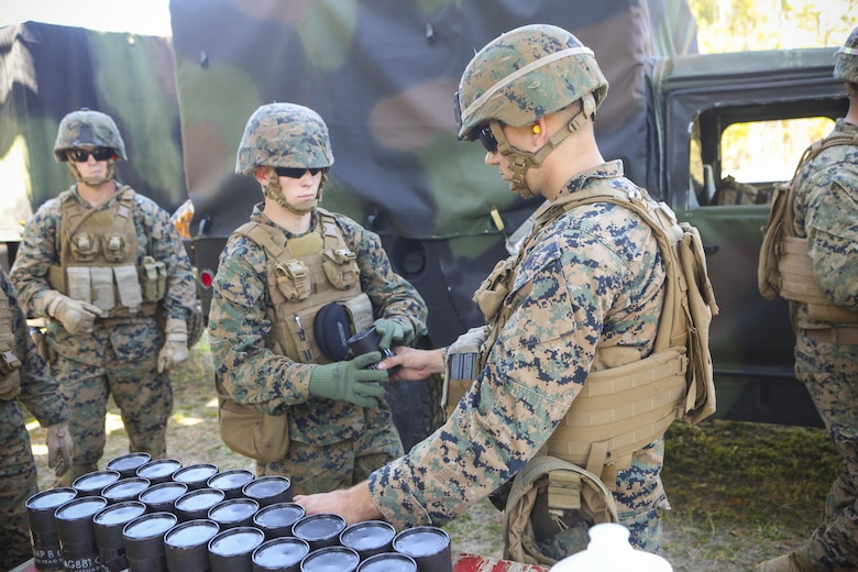 Marines with 2nd Law Enforcement Battalion receive their grenades before heading into the range pits at Camp Lejeune, N.C., March 16, 2016. This drill is part of an annual training event to prepare them for combat situations when they are called upon to deploy. Marines stood by the safety wall and waited to be escorted to the pits where they threw several grenades over the course of the afternoon. (U.S. Marine Corps photo by Lance Cpl. Aaron K. Fiala/Released)