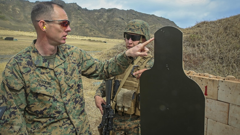 Gunnery Sgt. Nathan Stocking, the officer in charge for the Marine Corps Combat Shooting Team and a Phoenix, Ariz., native, provides feedback to another Marine on his missed rounds during the Pacific Combat Shooting Match at the Kaneohe Bay Range Training Facility at Marine Corps Base Hawaii, March 16, 2016. Teams from different units used various weapons and tactics to achieve the fastest time possible on different courses of fire, while earning points for awards during the competition. Marines from the Marine Corps Combat Shooting Team instructed and gave advice to the Marines participating in the event.