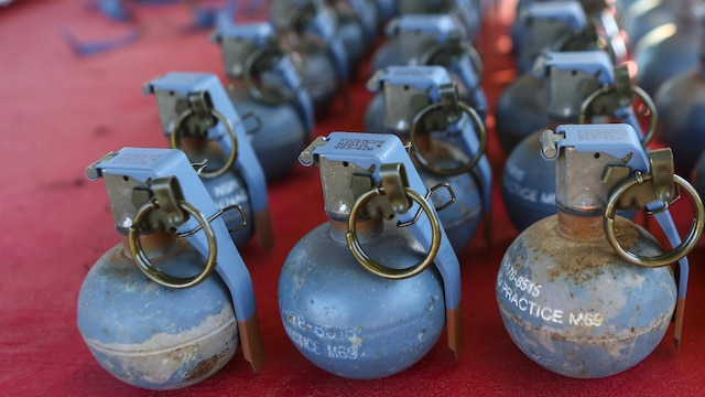 Inert grenades (dummy), non-exploding practice tools, sit on a table where Marines with 2nd Law Enforcement Battalion will pick them up before taking part in an assault course with grenade training at Marine Corps Base Camp Lejeune, N.C., March 16, 2016. This drill is part of an annual training event to prepare them for combat situations when they are called upon to deploy. Marines took turns providing cover fire for their partner, allowing them to throw a dummy grenade near the simulated enemy position.