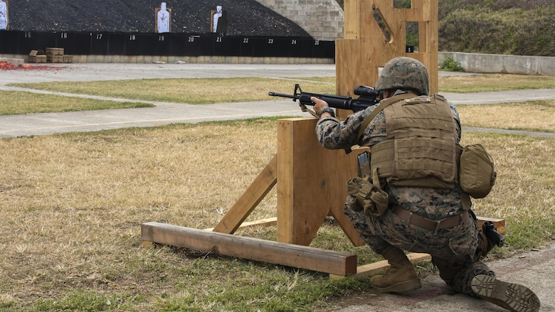 Cpl. Zachary Summers, a radio operator with 3rd Radio Battalion, kneels behind a barrier during a Pacific Combat Shooting Match at the Kaneohe Bay Range Training Facility at Marine Corps Base Hawaii, March 16, 2016. Teams from different units used various weapons and tactics to achieve the fastest time possible on different courses of fire, while earning points for awards during the competition. Marines from the Marine Corps Combat Shooting Team instructed and gave advice to the Marines participating in the event.