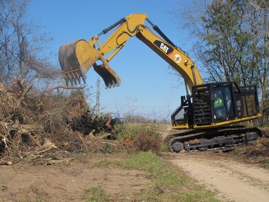 A backhoe removes trees and debris from one of two sites that will house the dissolved oxygen system on the Savannah River.