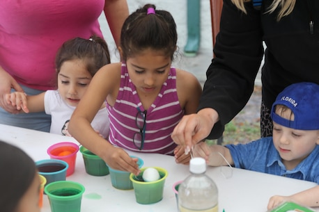 A young child paints an Easter egg during Recruiting Station Orlando's Easter Family Day March 19, 2016, Lakeland, FL. Children painted eggs the colors they desired with the assistance of their parents.