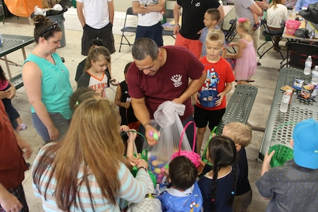 Sergeant Jason Gonzalez, supply clerk for Recruiting Station Orlando, passes out Easter eggs to children during RS Orlando's Easter Family Day March 19, 2016, Lakeland, FL. Gonzalez said he was happy that he could assist in bringing the children joy.