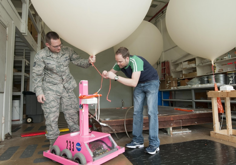 "Tech Sgt. Matthew Mong, a 45th Weather Squadron range weather forecaster, and Mike Boyer, a meteorological data specialist, attach a weather balloon to a ""weatherbot"" inside the weather balloon facility on Cape Canaveral Air Force Station, Fla., Feb. 24, 2016. The remote-controlled robot releases balloons when lightning is present so forecasters can stay safely indoors. Data from the balloons, particularly wind speed and direction, help Airmen and mission partners decide either to launch or postpone a space mission. (U.S. Air Force photo/Sean Kimmons)"