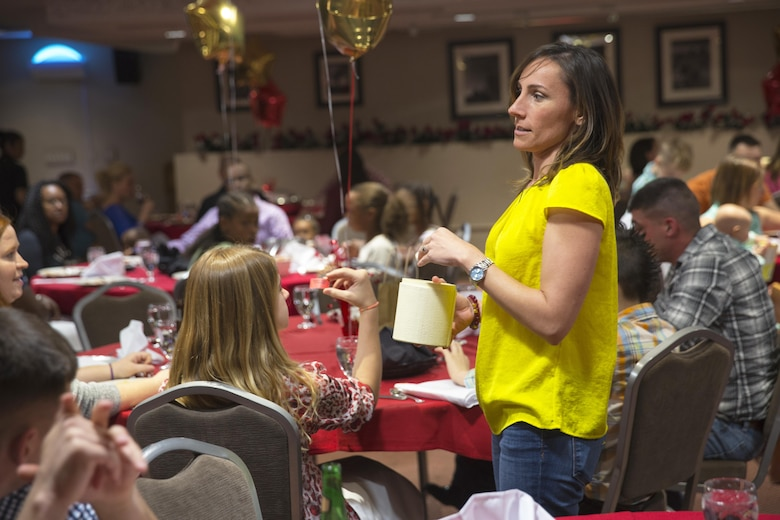 Bree Koumparakis, wife of Lt. Col. Speros C. Koumparakis, commanding officer, Communication Training Battalion, pulls raffle tickets during the battalion's first anniversary celebration at the Officer's Club March 10, 2016. The battalion, activated March 12, 2015, brought the training of enlisted and commissioned communication Marines under one command. (Official Marine Corps photo by Lance Cpl. Levi Schultz/Released)