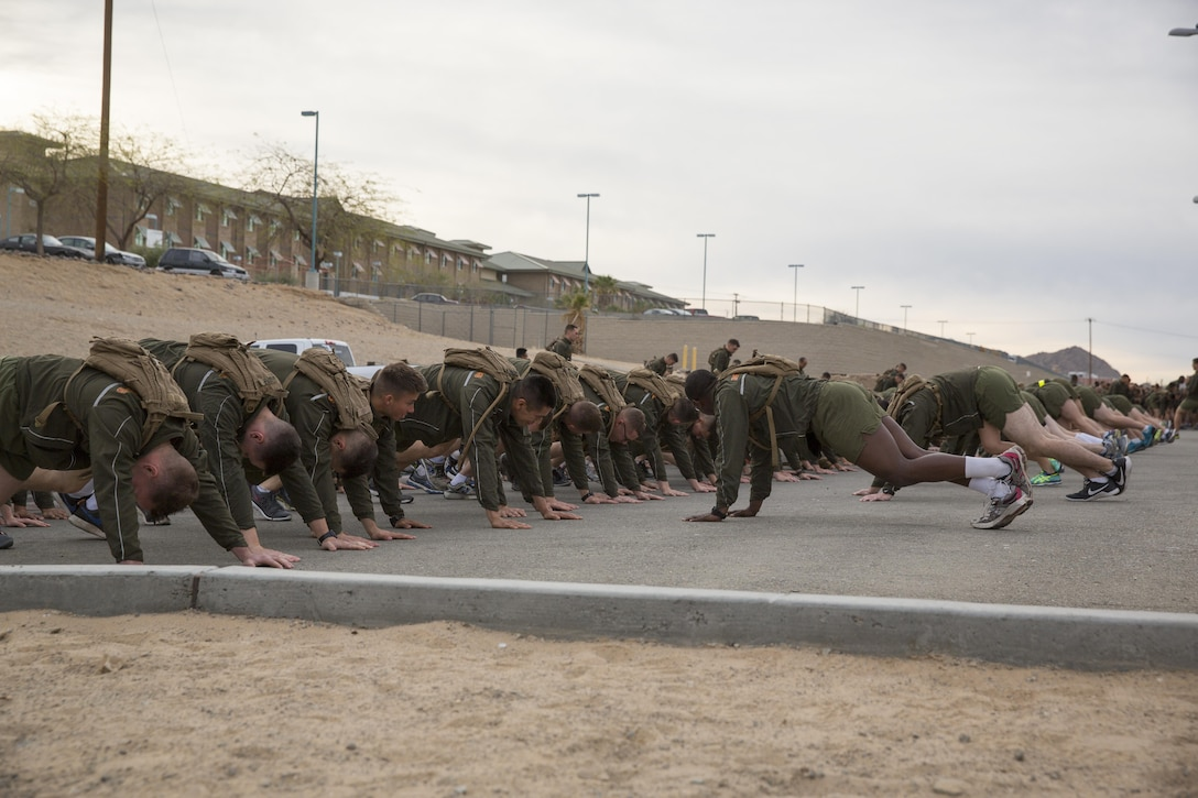 Marines with Communication Training Battalion, Marine Corps Communication-Electronics School, warm-up before participating in a three-mile motivational run in honor of the battalion's anniversary aboard the Combat Center March 11, 2016. The battalion, activated March 12, 2015, brought the training of enlisted and commissioned communication Marines under one command. (Official Marine Corps photo by Lance Cpl. Levi Schultz/Released)