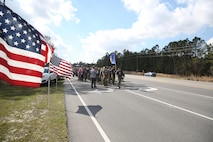 The local community lined the streets and cheered on the ruckers as they finished the Marine Raider Memorial March outside the Stone Bay main gate, aboard Marine Corps Base Camp Lejeune, N.C., March 21, 2016.  The Marine Raider Memorial March was designed to honor the seven Marine Raiders who died on March 10th, 2015 and their families, as well as bring awareness to their sacrifice. The ruckers were made up of both active duty and former Raiders, family members, and close friends. Following the conclusion of the March there was a short ceremony to honor the fallen.