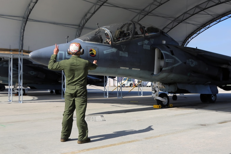 A plane captain communicates with the crew of an TAV-8B Harrier pilot prior to take off at Marine Corps Air Station Cherry Point, N.C., March 11, 2016. A plane captain is responsible for conducting a final examination of the aircraft and guiding the pilots out onto the runway. Plane captains possess extensive knowledge of their designated aircraft and can determine if there are any last minute discrepancies that could potentially ground the aircraft. (U.S. Marine Corps photo by Cpl. N.W. Huertas/Released)