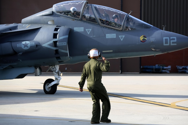 Lance Cpl. Viral Patel directs an TAV-8B Harrier pilot prior to take off at Marine Corps Air Station Cherry Point, N.C., March 11, 2016. A plane captain is responsible for conducting a final examination of the aircraft and guiding the pilots out onto the runway. Plane captains possess extensive knowledge of their designated aircraft and can determine if there are any last minute discrepancies that could potentially ground the aircraft. Patel is a plane captain and a fixed-wing aircraft mechanic with Marine Attack Training Squadron 203. (U.S. Marine Corps photo by Cpl. N.W. Huertas/Released)
