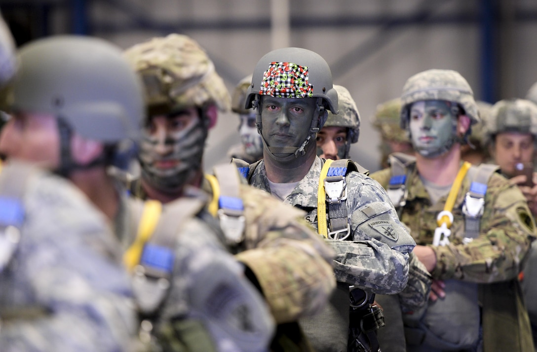 """Soldiers with the U.S. Army Reserve 412th Civil Affairs Battalion from Columbus, Ohio, form lines known as """"sticks"""" before walking out to the waiting U.S. Marine Corps KC-130J aircraft to conduct a jump over Wright-Patterson Air Force Base, Ohio, March 19, 2016. This jump was the first in almost 20 years to be conducted at Wright-Patterson by any unit. (U.S. Air Force photo by Wesley Farnsworth/Released)"""