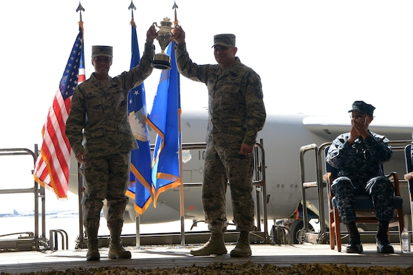 U.S. Air Force Col. Kristin Goodwin, 2nd Bomb Wing commander (left), and U.S. Air Force Chief Master Sgt. Tommy Mazzone, 2nd Bomb Wing command chief master sergeant (center), hold up the Omaha Trophy during an award ceremony honoring the 2nd Bomb Wing at Barksdale Air Force Base, La., March 21, 2016. During the ceremony, U.S. Navy Adm. Cecil D. Haney, U.S. Strategic Command (USSTRATCOM) commander (right), and Mr. W. Gary Gates (not pictured), Strategic Command Consultation (SCC) Committee member, presented the 2015 Omaha Trophy, strategic bomber category, to Goodwin and Mazzone in recognition of the wing's contributions to USSTRATCOM's global strategic missions. The Omaha Trophy, which dates back to the U.S. Air Force's Strategic Air Command, was originally created by the SCC in 1971. At the time, a single trophy was presented annually as a token of appreciation to USSTRATCOM's best wing. Since then, the tradition has evolved to unit-level awards that recognize the command's premier intercontinental ballistic missile (ICBM) wing, ballistic missile submarine, strategic bomber wing and global operations (space/cyberspace) unit. This year, a new category was added to include the combatant command's top strategic aircraft wing. (U.S. Air Force photo by Staff Sgt. Joseph A. Pagan Jr.)