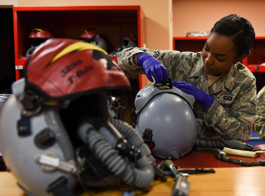 Airman 1st Class Kayla Stennis, 366th Operations Support Squadron aircrew flight equipment journeyman, adjusts pilots' helmets before takeoff at Mountain Home Air Force Base, Idaho, March 14, 2016. The helmets must be thoroughly inspected and in perfect condition before use. (U.S. Air Force photo by Airman Alaysia Berry/RELEASED)