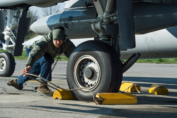 U.S. Air Force Airman 1st Class Jacob Johnson, a 74th Expeditionary Fighter Squadron crew chief, removes the blocks from the wheels of a U.S. Air Force A-10 Thunderbolt II during the 74th EFS's deployment in support of Operation Atlantic Resolve at Graf Ignatievo, Bulgaria, March 18, 2016. Johnson and his fellow 74th EFS crew chiefs ensure all aircraft are prepared and safe for flight before and after each flight. (U.S. Air Force photo by Staff Sgt. Joe W. McFadden/Released)