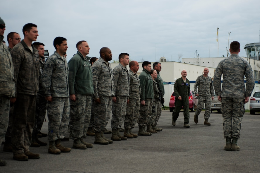 U.S. Air Force Lt. Col. Bryan France, 74th Expeditionary Fighter Squadron commander, center left, and Chief Master Sgt. Steven Cournoyer, 74th EFS chief enlisted manager, center right, walk to the front of a flight of mission support Airmen for a commander's call during the 74th EFS's deployment in support of Operation Atlantic Resolve at Graf Ignatievo, Bulgaria, March 16, 2016. The Airmen served in various communications, security forces, civil engineer, contracting, force support and logistics capacities to augment the 74th EFS's six-month deployment to Eastern Europe. (U.S. Air Force photo by Staff Sgt. Joe W. McFadden/Released)
